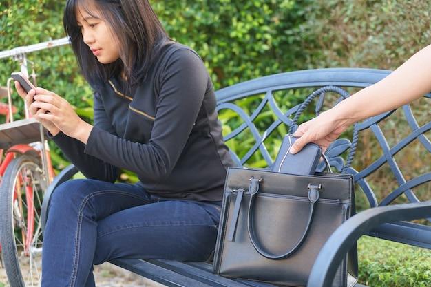 Ladro che cerca di rubare e allontana il portafoglio mentre la donna usa il cellulare