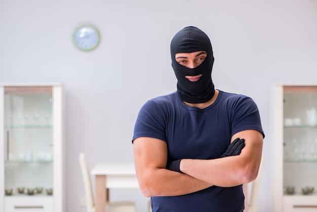 Ladro che indossa un passamontagna che ruba cose di valore