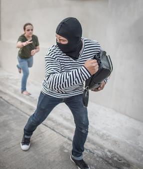 Ladro che ruba soldi e borsa dalle donne sulla via., concetti dei soldi del ladro