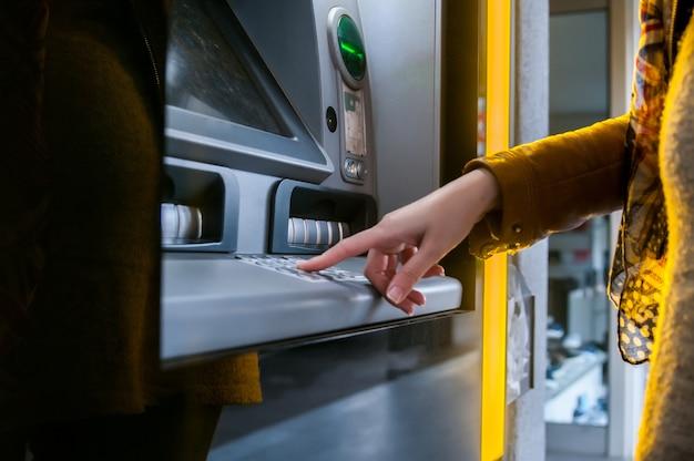 Lady che usa macchina atm per ritirare i suoi soldi.