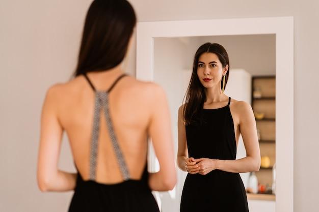Lady indossa un bellissimo abito nero guardando nello specchio