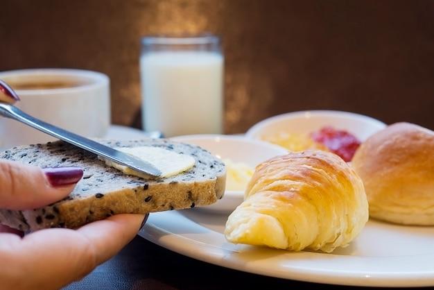 Lady mettendo il burro sul pane colazione set con latte e caffè