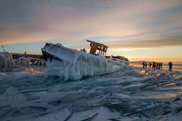 Lago baikal al tramonto, tutto è coperto di ghiaccio e neve, denso ghiaccio blu chiaro