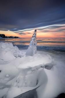 Lago baikal al tramonto, tutto è coperto di ghiaccio e neve, denso ghiaccio blu chiaro.