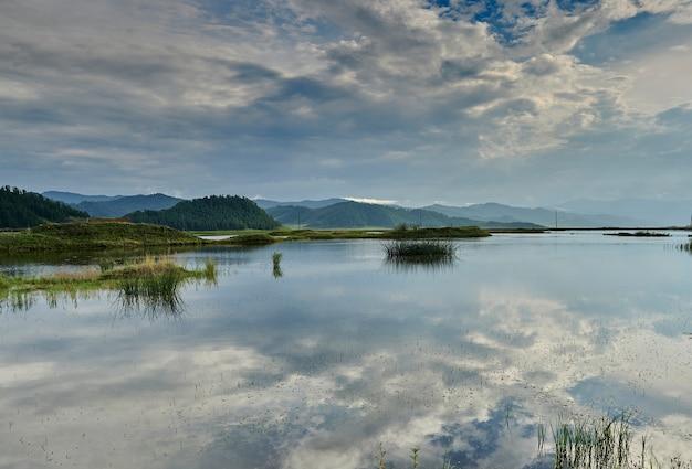 Lago con riflesso del cielo e canne circondato da montagne. altai