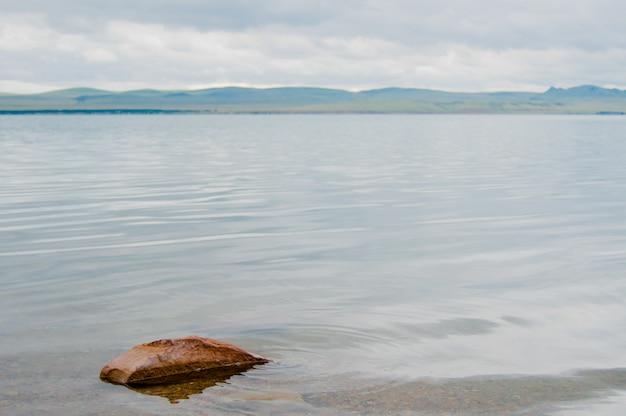 Lago e fiume di fronte con alcune montagne