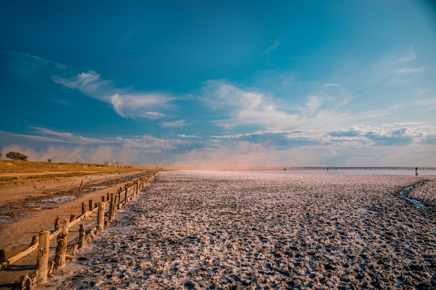 Lago e spiaggia sabbiosa rosa con una baia del mare sotto un cielo blu con le nuvole