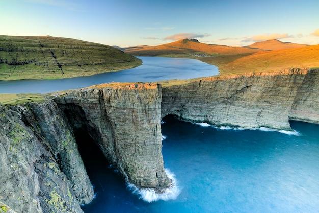 Lago leitisvatn e tralanipan, roccia schiava al tramonto. isola di vagar, isole faroe. danimarca
