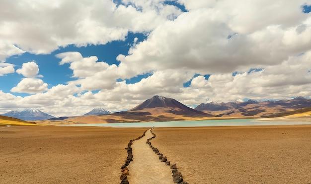 Lago miscanti e catena montuosa nel deserto di atacama. percorso di pietra e sabbia in primo piano. regione di antofagasta. chile