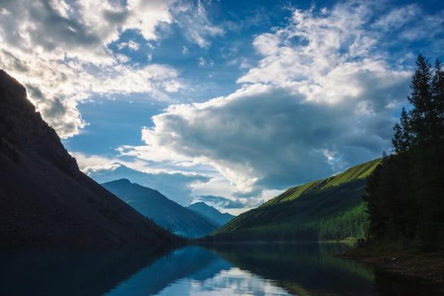 Lago spettrale della montagna in altopiani al primo mattino. belle sagome nebbiose di montagne e nuvole riflesse nella chiara superficie dell'acqua. fumo di fuochi. incredibile paesaggio di natura maestosa.
