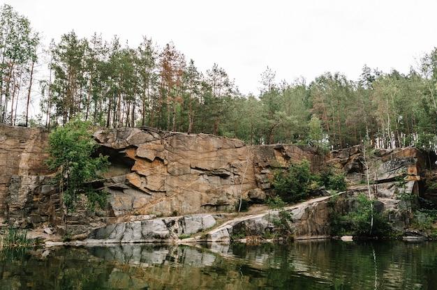 Lago sulla superficie delle rocce e degli abeti