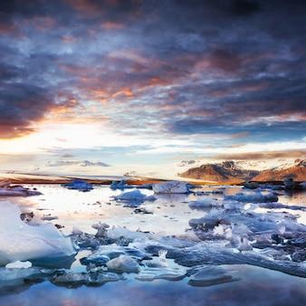 Laguna del ghiacciaio jokulsarlon, fantastico tramonto sulla spiaggia nera,