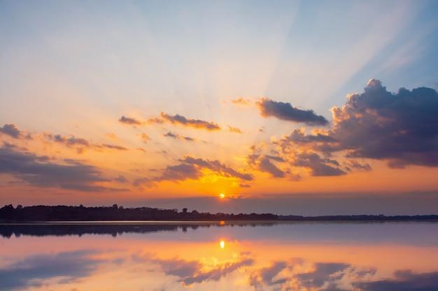 Laguna di riflessione al tramonto. bel tramonto dietro le nuvole e il cielo blu sopra il paesaggio della laguna