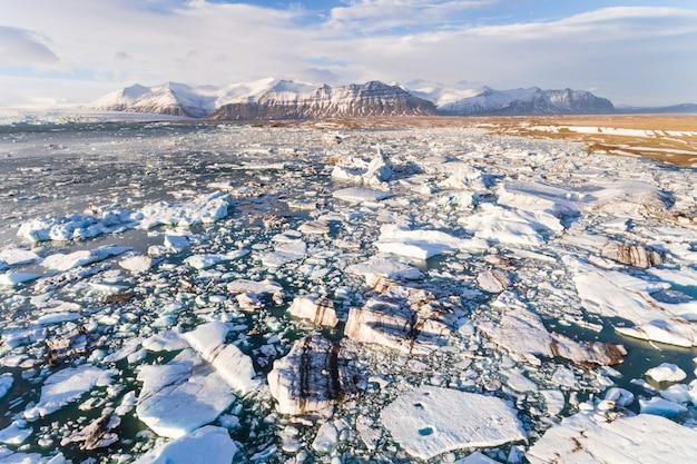 Laguna glaciale di jokulsarlon con iceberg galleggianti e montagne