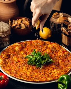 Lahmajun turco con carne, erbe e succo di limone