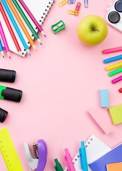 Laici piatta di ritorno a scuola di articoli di cancelleria con mela e matite colorate
