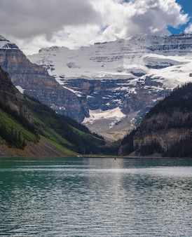 Lake louise con la copertura di montagna da neve sui precedenti nel giorno di estate soleggiato