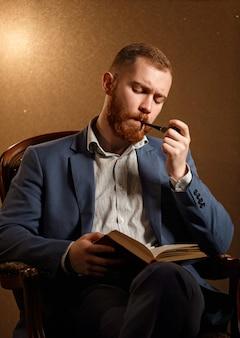 Lamber barbuto come modello maschile in tuta con baffi e barba che fuma la pipa e leggere il libro mentre era seduto sulla sedia.