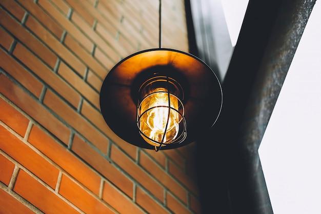 Lampada a led vintage o lampadina a incandescenza in ristorante o bar con antica parete a blocchi con tonalità marrone e arancione.