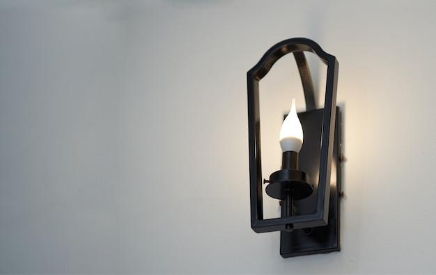 Lampada da parete con montatura in metallo e lampadina in basso