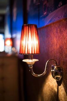 Lampada da parete in un locale notturno. bella luce soffusa dalla lampada