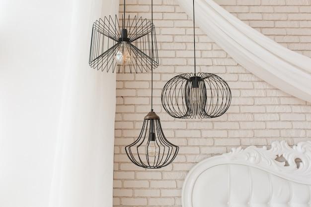 Lampada da soffitto con design nero sospesa nella camera da letto. loft dettagli interni