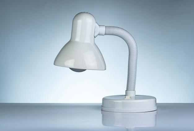 Lampada da tavolo moderna bianca isolata sulla tavola bianca sul fondo di pendenza. lampada da scrivania per la lettura di un libro in dormitorio. mobili per la casa e l'ufficio dal design minimalista. faretto da scrivania.