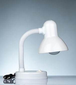 Lampada da tavolo moderna bianca scollegata isolata sulla tavola bianca sul fondo di pendenza. lampada da scrivania per la lettura di un libro in dormitorio. mobili per la casa e l'ufficio dal design minimalista. faretto da scrivania.