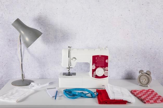 Lampada vicino alla macchina da cucire sul tavolo