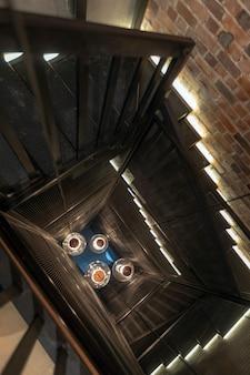 Lampade a sospensione giganti al centro della scala a chiocciola con muro di mattoni rossi