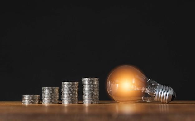 Lampadina a risparmio energetico con pile di monete per il risparmio