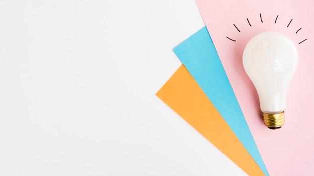 Lampadina bianca su carta artigianale colorata con sfondo bianco spazio copia