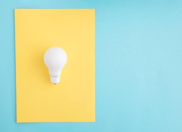 Lampadina bianca su carta gialla su sfondo blu