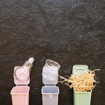 Lampadina, bicchiere di plastica e legno sul pattumiera in miniatura colorato