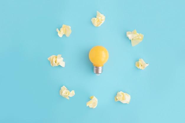 Lampadina circondata con carta sgualcita giallo su sfondo blu