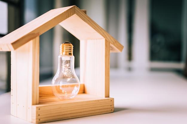 Lampadina con casa in legno sul tavolo.