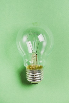Lampadina con filamento incandescente su sfondo verde
