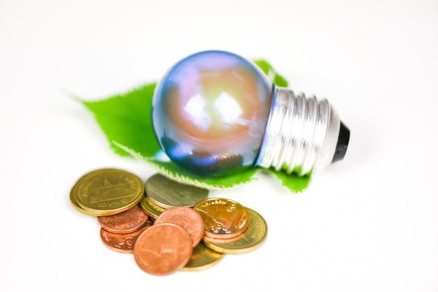 Lampadina con luce dalla lampada con la foglia e la moneta verdi su fondo bianco - idea economizzatrice d'energia, risparmio energetico e il concetto del mondo