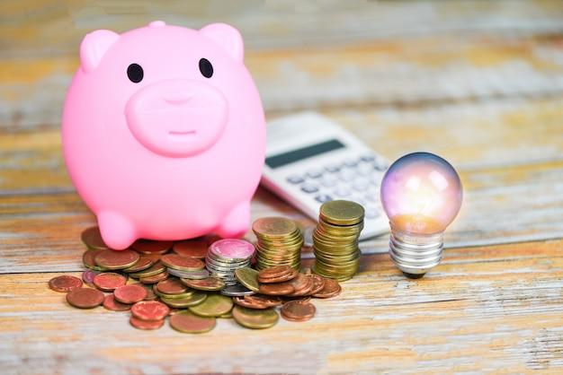 Lampadina con luce dalla lampada e moneta salvadanaio sul tavolo di legno