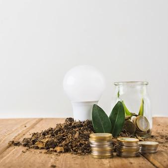 Lampadina con vaso di vetro e pile di monete