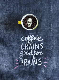 Lampadina del ritaglio di carta dentro i chicchi di caffè nella tazza con testo sulla lavagna
