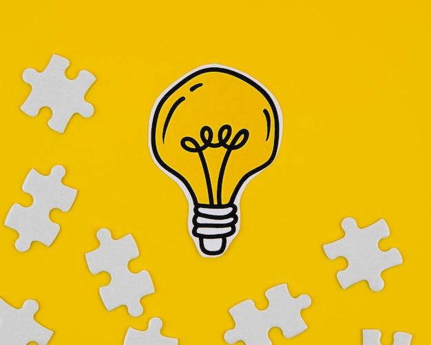 Lampadina dorata del primo piano con i pezzi di puzzle