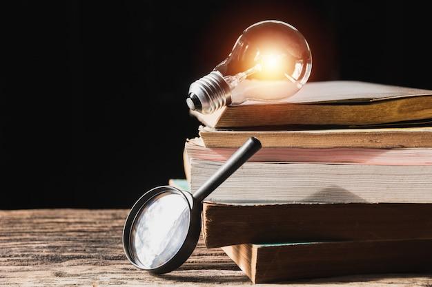 Lampadina e pila di libro sul tavolo di legno