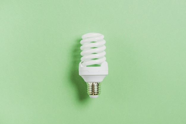 Lampadina fluorescente compatta su sfondo verde