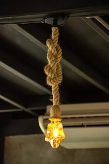 Lampadina gialla la stella è appesa a una corda.