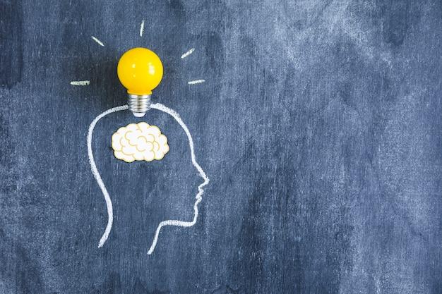 Lampadina gialla sopra il cervello del ritaglio di carta sul fronte del profilo fatto con gesso sopra la lavagna