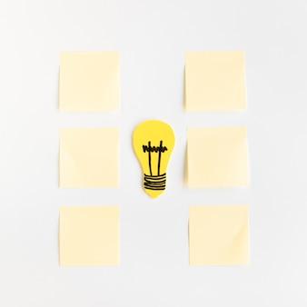 Lampadina gialla tra le note adesive disposte in fila