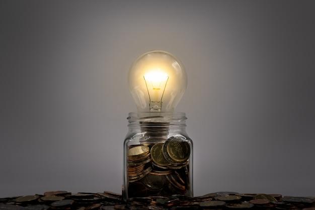Lampadina incandescente sulle monete in barattolo di vetro