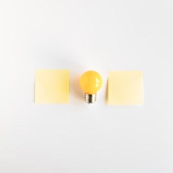 Lampadina tra due note adesive su sfondo bianco