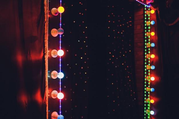 Lampadine sul palco scena teatrale con lampadine al neon colorate glitter per presentazioni o concerti. spettacolo notturno in serata festiva.